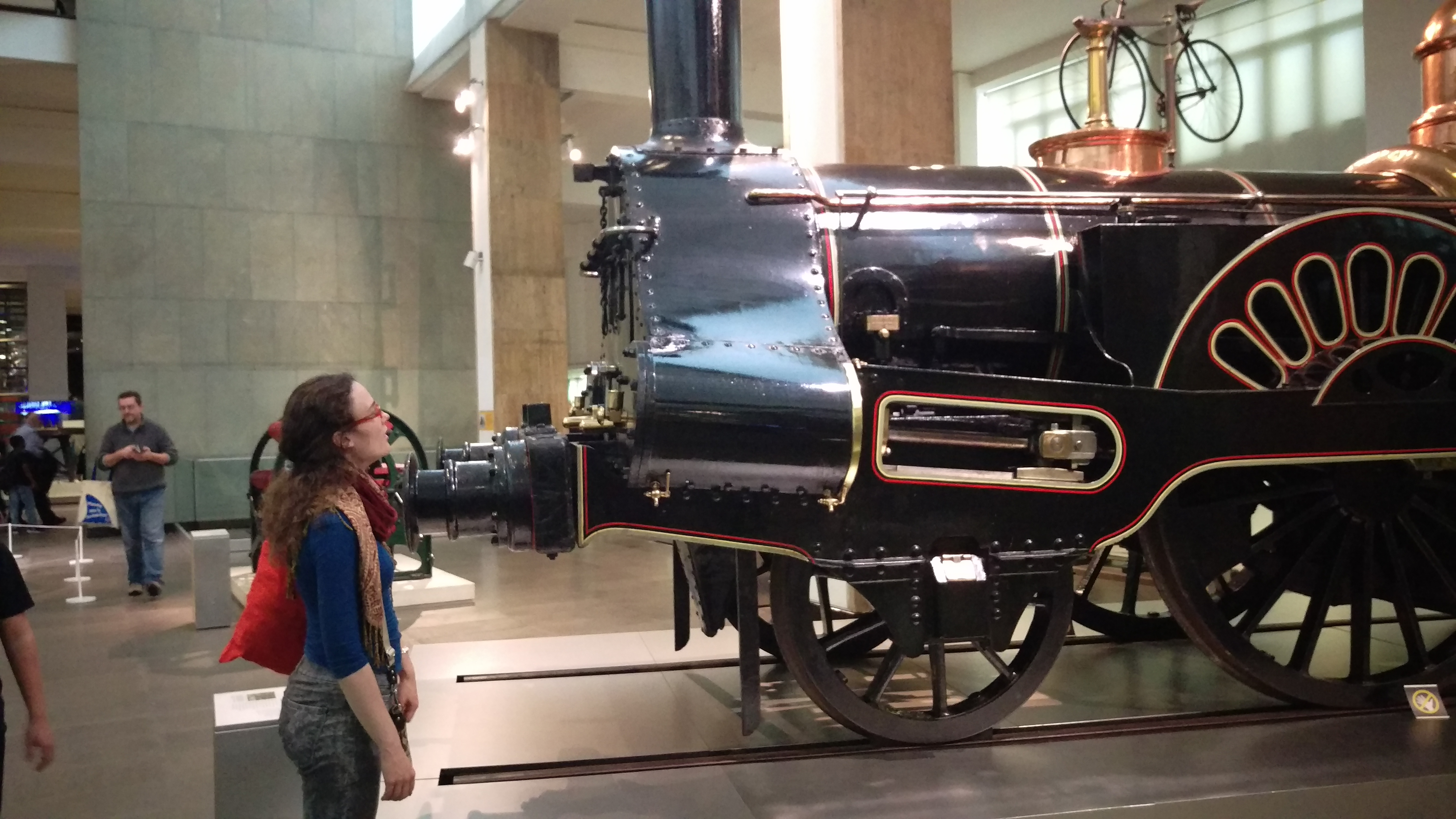A photo of me, starting with mouth agape at a train from the industrial revolution era in the London Science museum